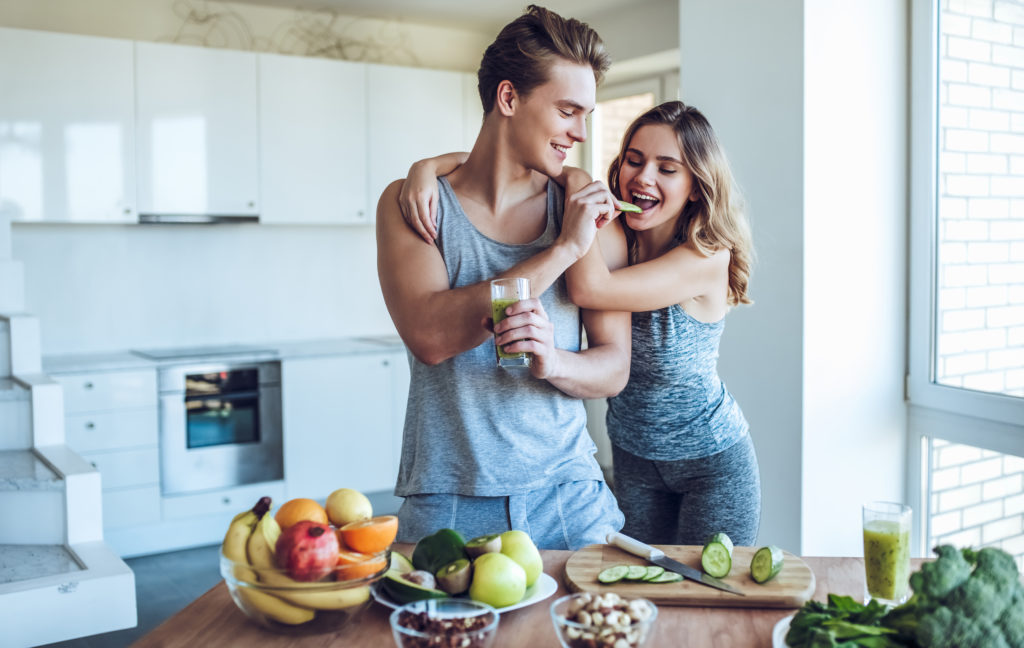 young fit couple eating healthy food in kitchen